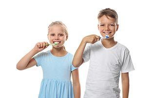 Children brushing teeth on white background