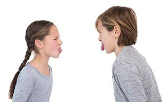 Children sticking their tongue out in a fight